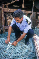 An inspector measures the mesh of a trawl net, part of monitoring efforts