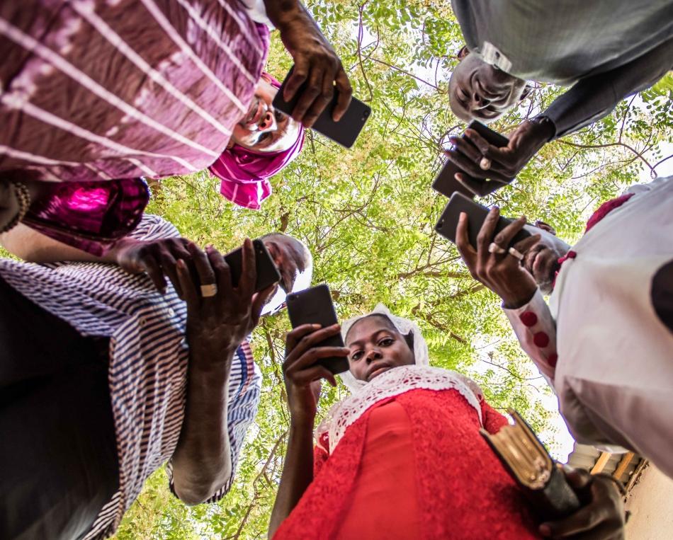 Grupo de personas miran su telefono movil en circulo | sembralia