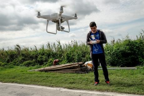 Chico joven controla un dron blanco en un cultivo | sembralia