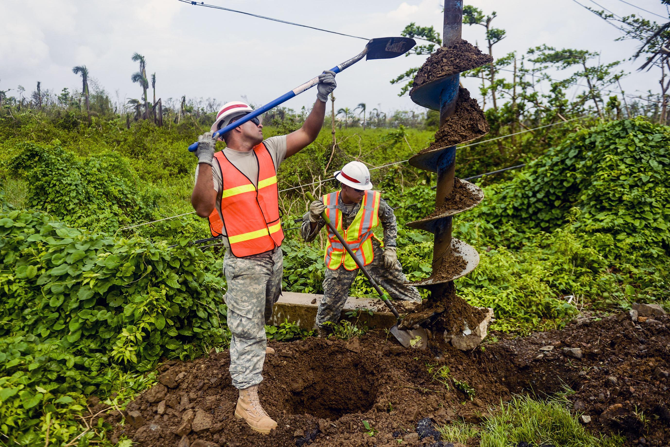 Luis Ruiz, left, and Jonathan Quinonez clean the dirt off an auger as they dig a hole to place a concrete power pole in Rio Grande, Puerto Rico