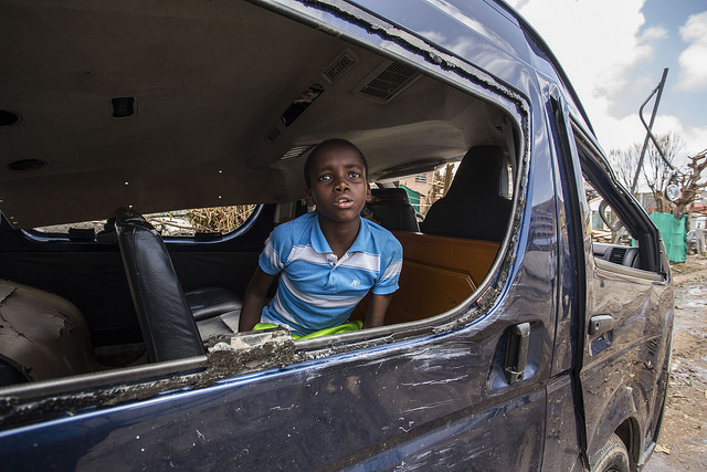 A boy looking through a window in St. Maarten after Hurricane Irma
