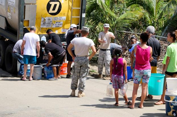 Puertorriqueños esperan en una cola para recibir agua.