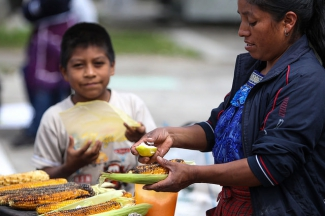 A woman preparing roasted corn in Mexico