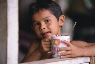 Young boy takes a drink of homemade cocoa in Brazil
