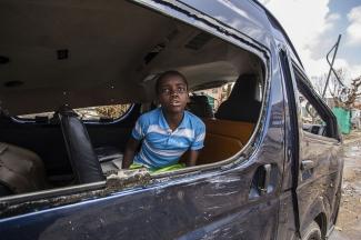 Un niño mira por la ventana en St Maarten tras el huracán Irma