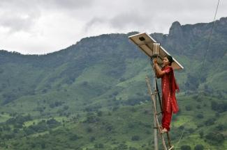 Una chica realiza trabajos de mantenimiento en los paneles solares de la calle en Tinginaput, India.