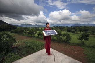 Indian girl holding a solar panel