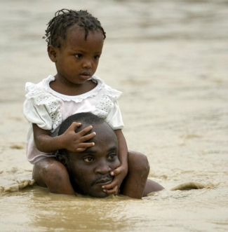 A father carries his daughter on the shoulders as residents flee rising waters in search of shelter after heavy rains caused by tropical storm 'Noel' flooded their homes in Cité Soleil Haiti.