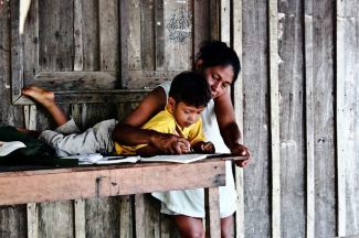 A mother in the indigenous community of Macedonia, in the Colombian Amazon teaching her son how to read and write
