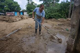 Magaly Sánchez comienza a limpiar los escombros de la inundación alrededor de su casa en Puerto Rico