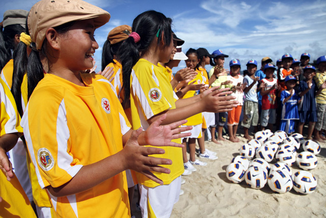 Children attending a soccer demonstration in a community helped by FAO and AFC