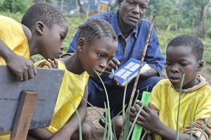 Children measuring their onion plants during a Junior Farmer Field School session in Mbaiki, Central African Republic. The children are orphans and came up with a plan to plant onions during the rainy season. They also discuss nutrition and learn other life skills.